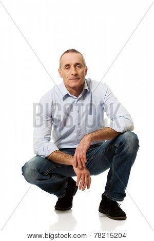 Happy handsome mature man squatting.