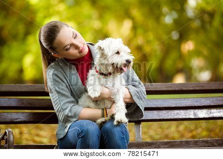 Beautiful female in park with her dog breed maltese