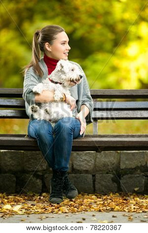 Young woman with a maltese dog sitting in park