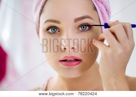 Close up of young beautiful  woman applying mascara