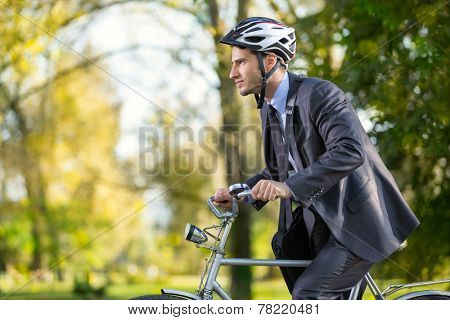 Young business man on a bike hurry to work