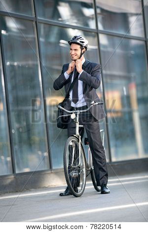 Businessman puts the bicycle helmet on head protection on bicycle