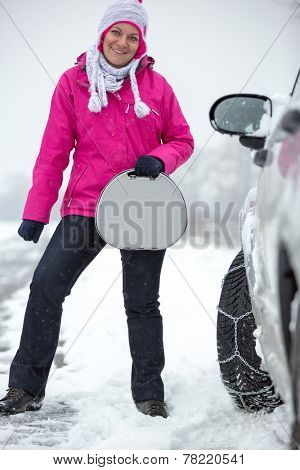 smiling woman standing next her car with snow chains on tire