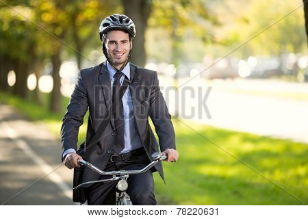 young smiling businessman riding a bicycle to work, concept  gas savings concept