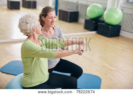 Senior Woman Assisted By Personal Trainer In Gym