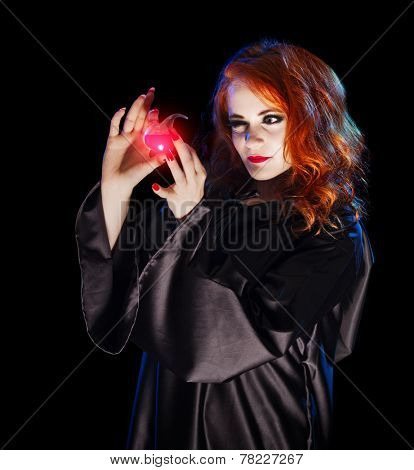 Young witch with potion isolated