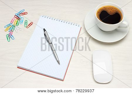Office table with notepad and coffee cup