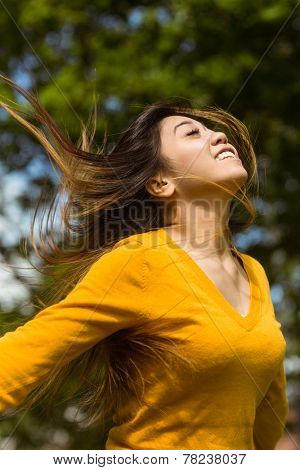 Side view of beautiful young woman with arms outstretched in the park