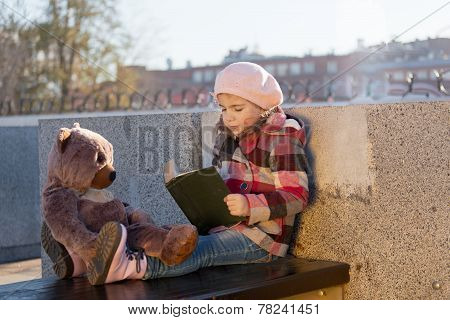 Little girl sits on a bench and reads the book to a toy bear