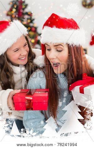 Festive mother and daughter exchanging gifts against snow falling