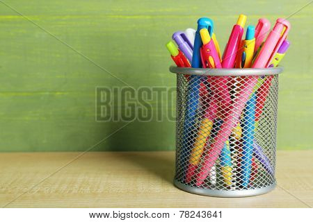 Metal holder with different pens on wooden table and green wooden background