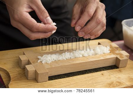 Closeup of chef putting japanese sushi roll