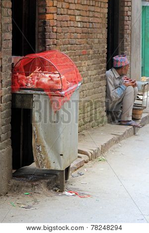 PATAN, NEPAL - APRIL 2014 : A Nepalese man waiting for customers to buy his poultry on 13 April 2014 in Patan, Nepal. It is a common scene to buy fresh meat on the street.