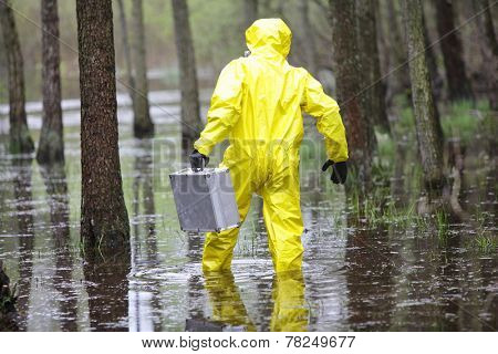 Technician in professional uniform with silver suitcase  in contaminated  floods area - back view