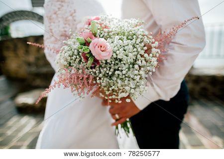 Wedding Bouquet In Groom's And Bride's Hands Closeup
