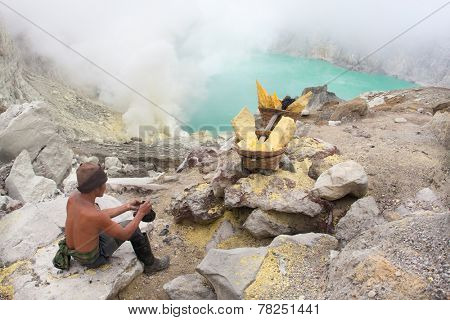 BANYUWANGI, EAST JAVA NOV 12:Sulphur miner taking a break before climbing out of the Ijen crater with his baskets of hardened sulphur on Nov 12, 2012, Ijen volcano, East Java, Indonesia.