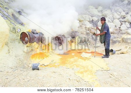 BANYUWANGI, EAST JAVA NOV 12 : Sulphur miner using metal crowbar to prise off hardened sulphur from the ground to be collected and sold on Nov 12, 2012, Ijen volcano, East Java, Indonesia.