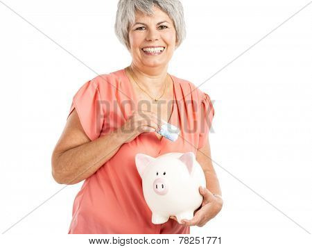 Portrait of a happy old woman putting money on  a piggy bank, isolated on a white background