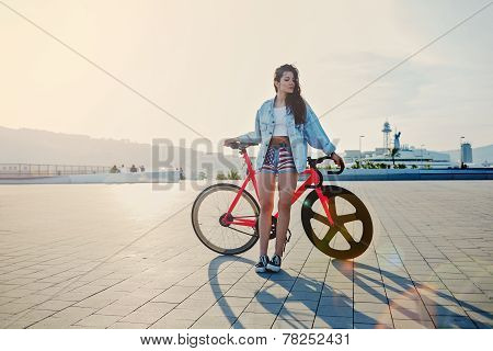 Pretty young brown haired woman standing with her modern pink bicycle at sunset