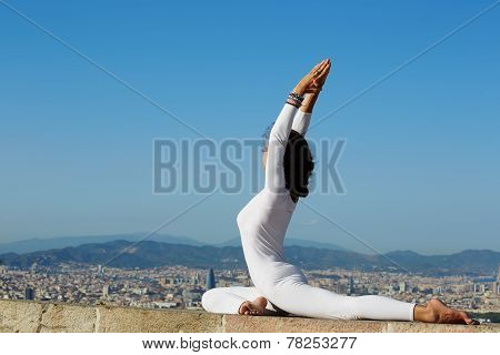 Yoga on high altitude with big city on background woman stretching seated in yoga pose