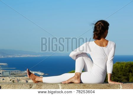 Yoga on high altitude with big city on background young woman seated in yoga pose on amazing city ba