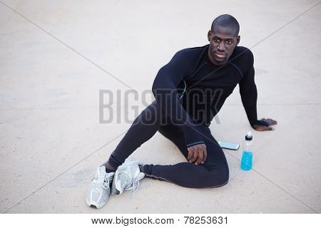 miling dark skinned runner resting after workout outdoorsmale runner in active clothes taking break