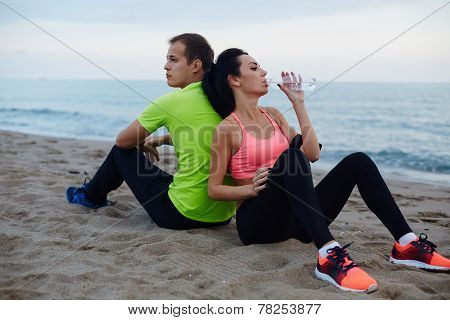 Exhausted after run resting couple of two runners sitting on the beach living healthy