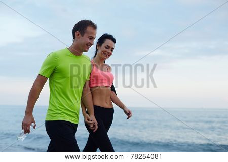 Sport couple walking along the beach resting after workout, sexy fit woman and man taking break
