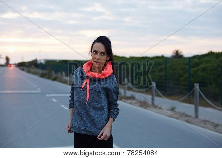 Fitness woman dressed in bi color hoodies standing on the road at sunset