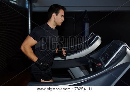 attractive sportsman at the gym doing exercise on the treadmill handsome brunette man doing workout