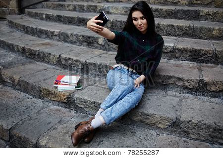 Laughing student girl taking a self portrait with smart phone