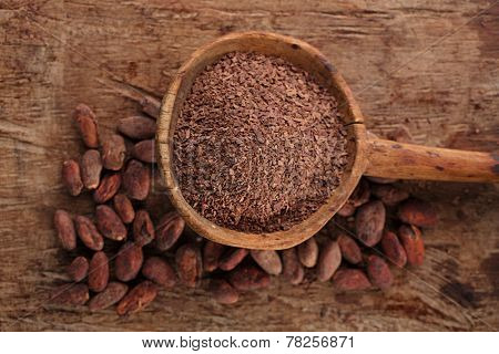 grated dark chocolate in old wooden spoon on roasted cocoa chocolate beans background