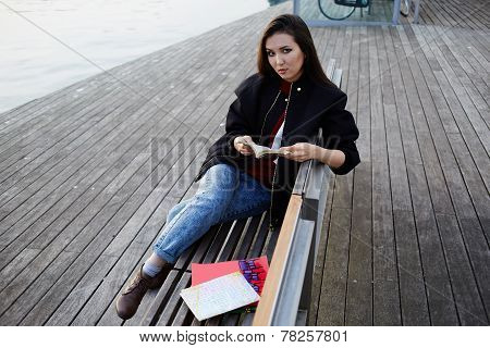 Beautiful girl holding an open book sitting on wooden bench near artificial lake