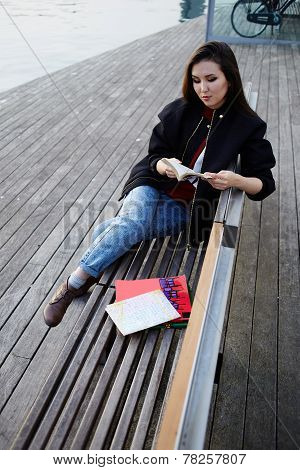 Vacation holiday in Barcelona young female traveler sitting on wooden bench read some book