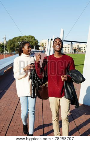 Full length of cheerful university students walking on campus young
