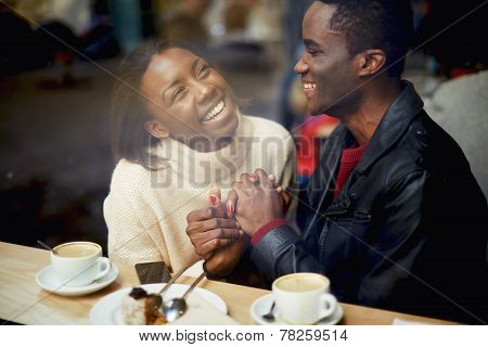 Romantic couple having fun together best friends smiling sitting in cafe view through cafe window