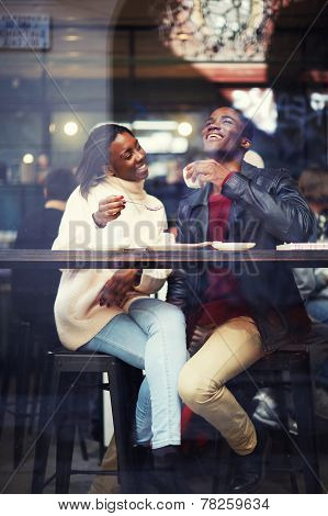 Beautiful couple in love drinking coffee and laughing in coffee shop, happy friends having coffee