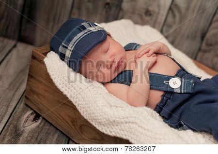 Newborn Baby Boy Wearing A Newsboy Cap And Suspenders