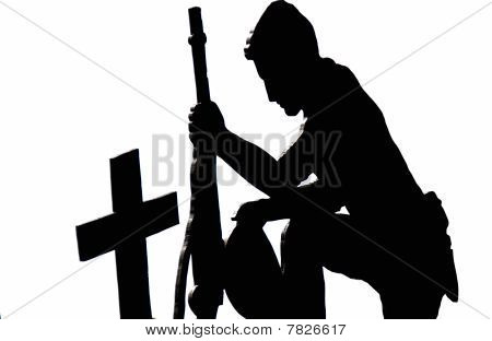 Silhouette of Soldier kneeling at grave