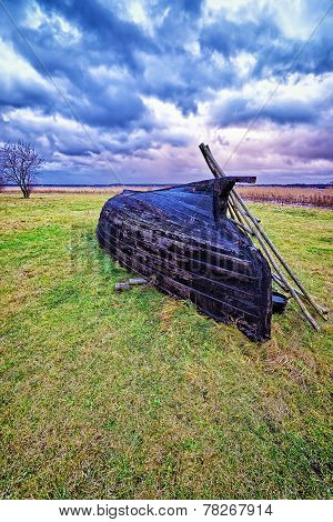 Overthrown Fisherman Boat On The Lake Shore At Stormy Weather
