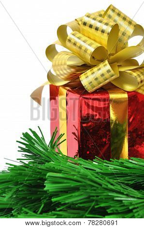 Red gift with gold bow and christmas tree