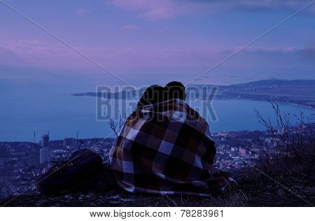 Couple In Love Sitting On Hill Above The City In Night