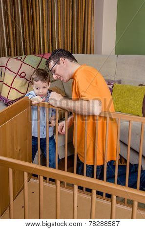 Father and son assembling cot for a newborn at home