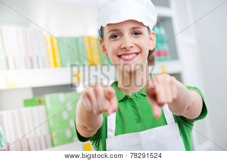 Sales Clerk Smiling And Pointing At Camera