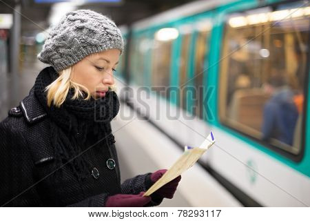 Lady waiting on subway station platform.