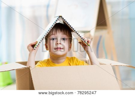 kid boy playing in a toy house