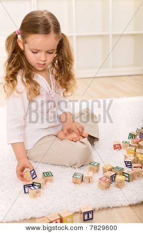 Kleine Mädchen spielen mit Holzklötzen