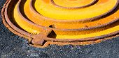 foto of manhole  - Rusty metal manhole cover in black asphalt surface - JPG