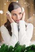 stock photo of muff  - Pretty brunette with ear muffs thinking against green fir branches with snow - JPG