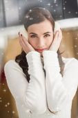 stock photo of muffs  - Pretty brunette with ear muffs against twinkling stars - JPG